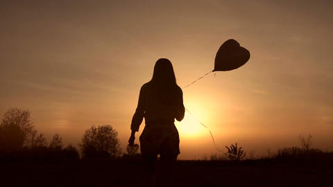 Silhouette of young woman with balloon at sunset Footage