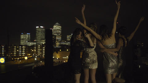 Female friends party on rooftop at night Footage