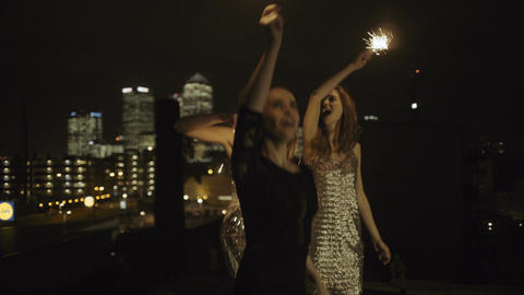 Female friends party on rooftop at night with sparklers Footage