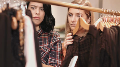 Young adult women looking at clothes in shop Live Action