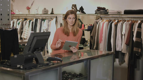 Small business owner in clothes shop working on digital tablet Footage