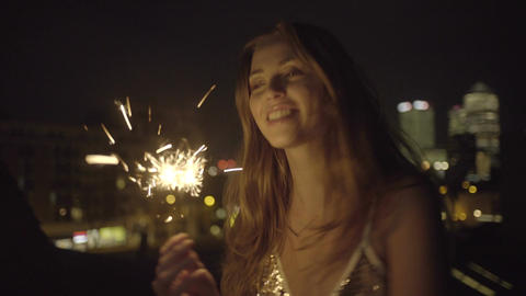Young adult woman dancing on rooftop with sparkler Footage