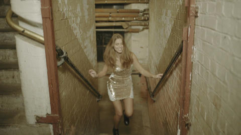 Young adult woman running up stairs in warehouse Footage