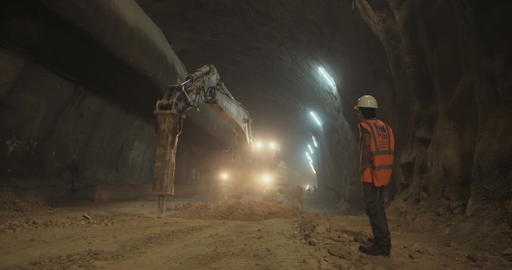 Construction work inside a highway tunnel with workers and heavy tools Footage