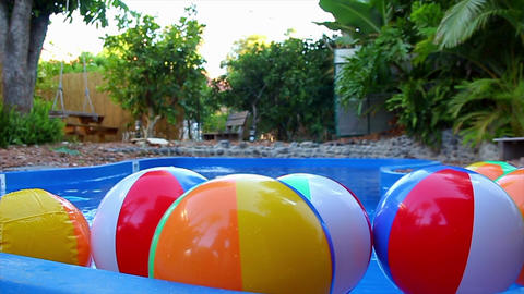 Colorful beach balls floating in pool in slow motion Footage