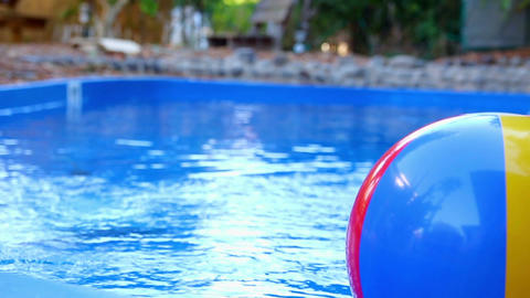Colorful beach ball thrown into the water in the pool Footage