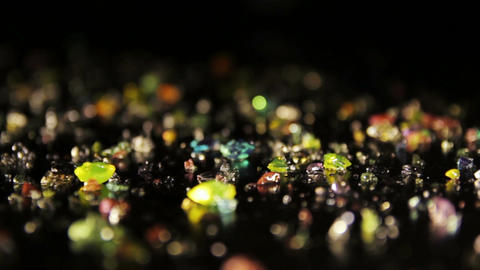 Diamond-shaped colored crystals scattered on a black table. Pan shot Footage