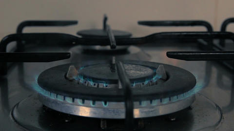 Frying pan being put on a kitchen gas stove with gas burning - Dark closeup Footage