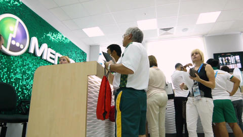 People Stand at Reception with Large Megafon Brand Background Footage