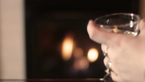 Woman sets down Wine glass in front of bokeh luxury fireplace in hotel Footage