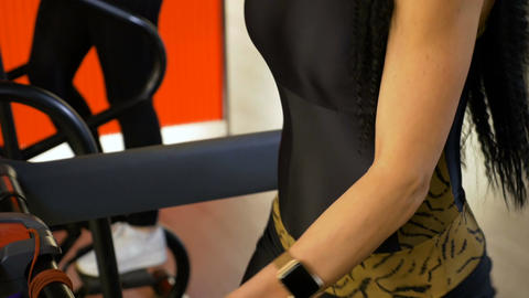Closeup of slim attractive woman with smart watch doing weight loss exercises on Live Action