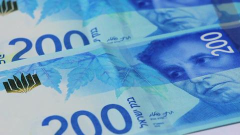 Stack of Israeli money bills of 200 shekel - Tilt up Footage