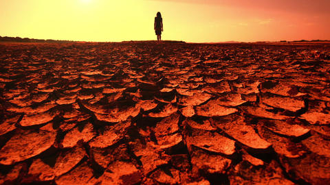 Global warming concept. Young woman walking across desert Footage