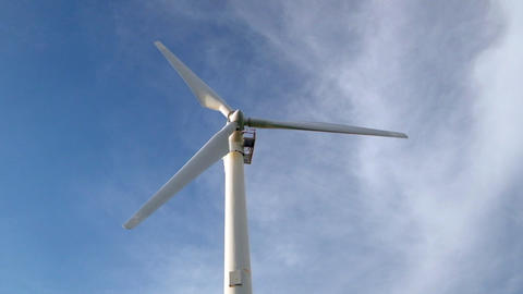 Wind turbine rotating over blue sky generating green energy Footage