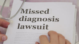 Doctor Holding Missed Diagnosis lawsuit papers Footage
