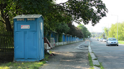 modern latrine next to the road in the city - passing cars - city in background  Footage
