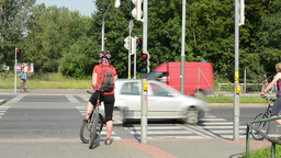 cyclists and pedestrians waiting at traffic lights - busy urban street with cars Footage