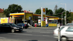 gas station Shell in the city - with cars and people. Passing cars in foreground Footage