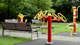 senior park (exercise machines) with benches - in the park with trees and grass  Footage