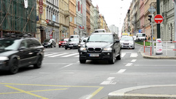 urban street with passing cars and pedestrian crossing: people walking - buildin Footage