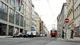 urban street with passing cars and tram- pedestrian crossing: people walking - b Footage