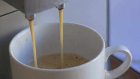 Close-up coffee machine pour espresso in white cup Footage