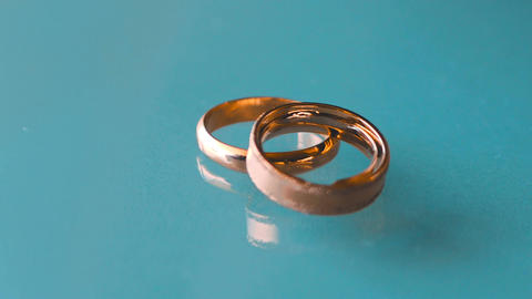 Wedding rings on a blue marble table Footage