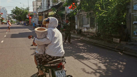 People on Motorbike Drives along Street in Sunny Morning Footage