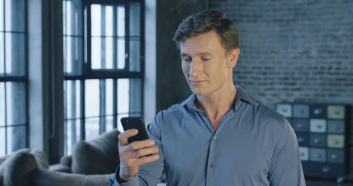Slow Motion Portrait of Successful Confident Businessman Using Smartphone Apps a Footage