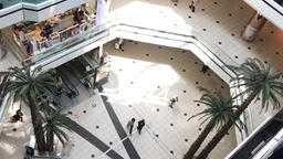 People walk near escalators on few levels of shopping center, view from above