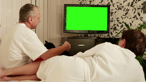 Couple sitting on the couch and watching TV with green screen Footage