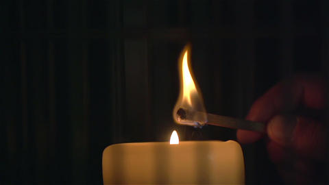 Lighting a candle with match in slow motion. Close Up Live Action