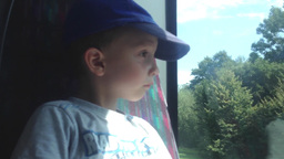 small child (boy) travel by bus and looks out the window at the urban street wit Footage