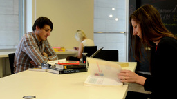 people study in the classroom and a woman enters to the room and walk, sit, open Footage