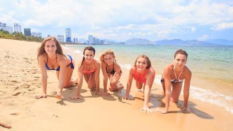 cheerleaders in bikinis crawl in line along sand beach smile Footage