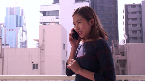 Young Chinese Asian Businesswoman Talking On Phone Near Office Buildings Footage