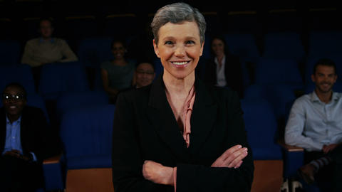 Confident businesswoman standing with arms crossed in auditorium Live Action