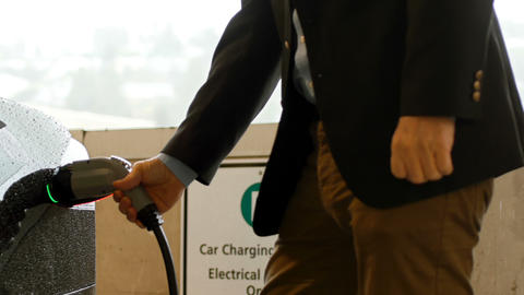 Man charging the electric car Live Action