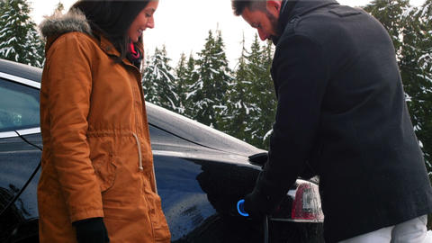 Couple talking while charging the electric car on a snowy day Footage