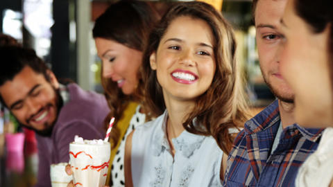 Group of friends interacting while having milkshakes Live Action