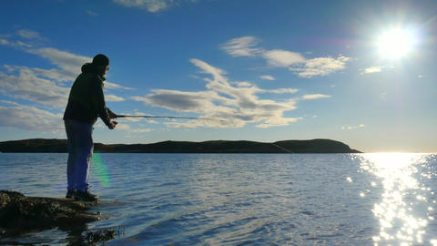 Very close rear view to working fisherman. Man check pushing bait and throws it  Footage