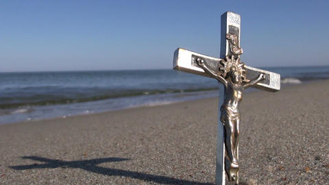 Metal crucifix on summer sea beach, religion concept Footage