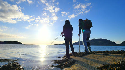 Friends talk about fishing and health. Young working fisherman on stone at sea l ビデオ