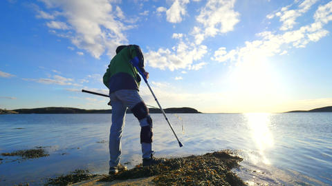 Fisherman with medicine crutch and broken knee fixed in immobilizer is fishing.  Footage