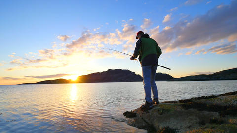 The active man is fishing on sea from the rocky coast. Fisherman check pushing b Footage