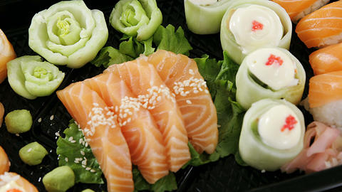 Sushi rolls with salmon in plastic tray Live Action