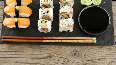 Set of assorted sushi served on black stone slate Footage