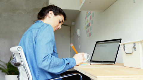 Female executive writing on sticky notes at desk Live Action