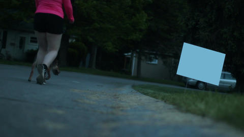 Woman and dog walk past blank ominous evil political sign Live Action