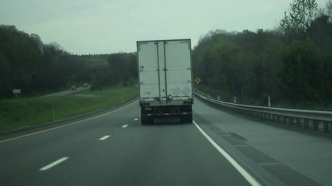 Driving behind a eighteen wheeler on a two lane highway on overcast day Footage